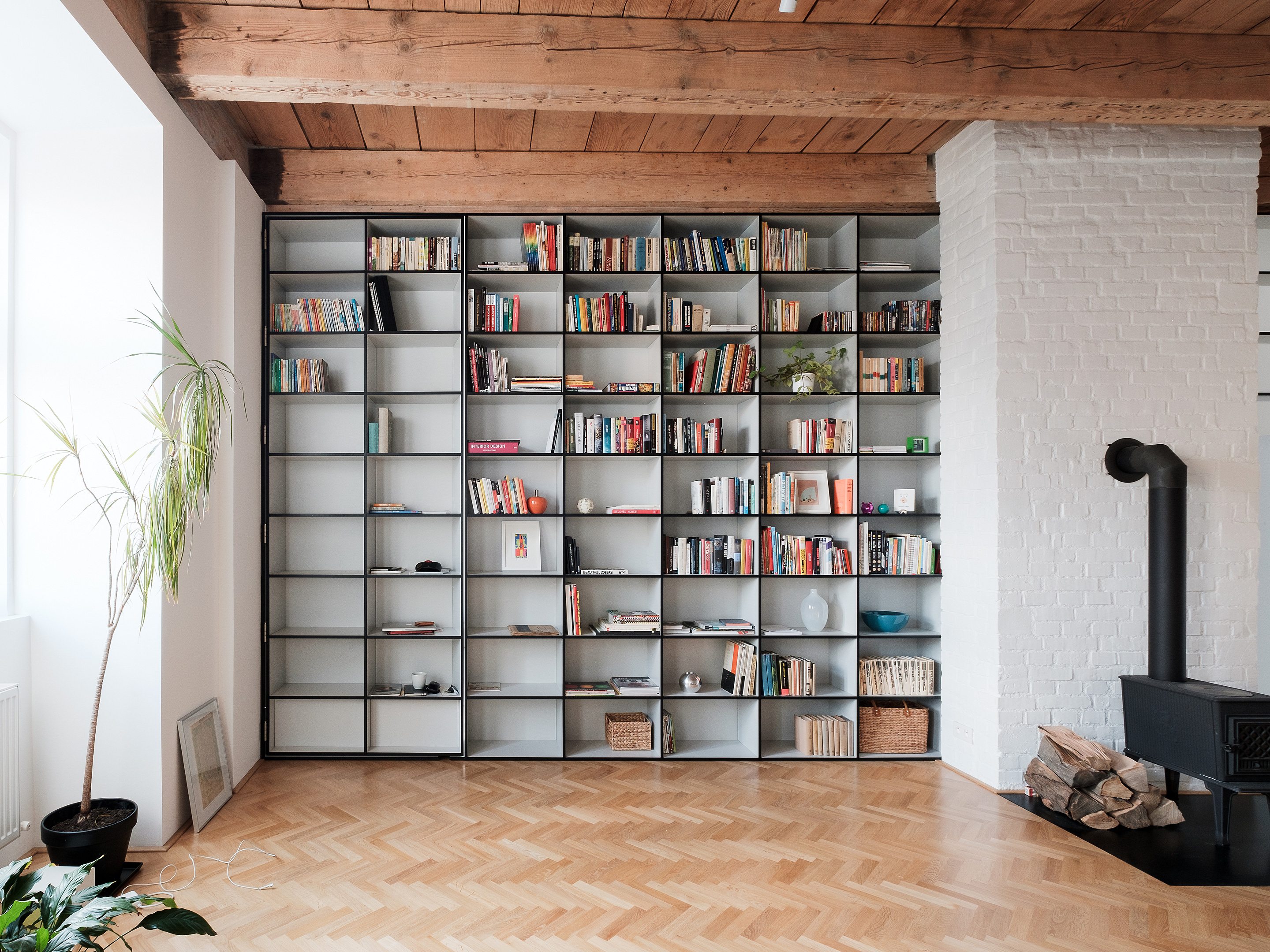 JRKVC Designed Clean And Functional Apartment Using Full Height Bookshelf  As A Space Divider: JRKVC