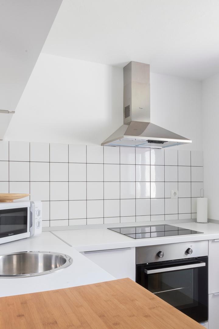 Apartment for daily rent   interior design   kitchen   light kitchen   white tiles   black grouts   neutral palette